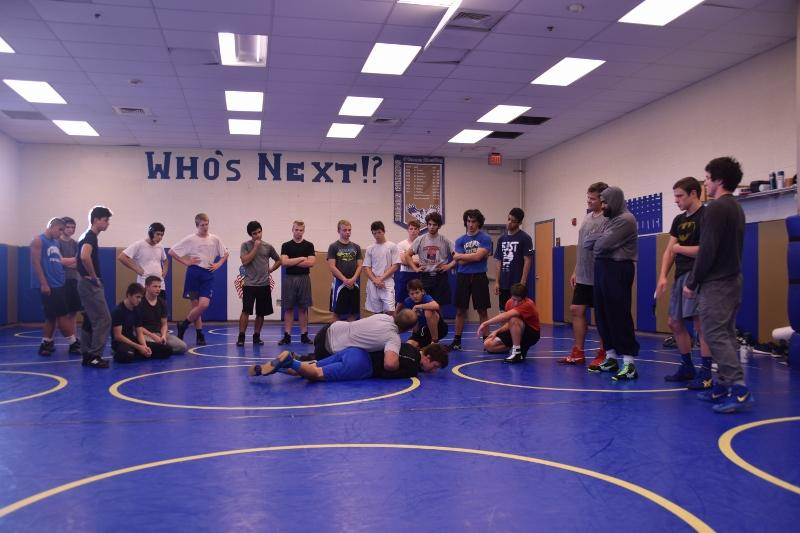 Coach+John+DeVito+pins+down+varsity+wrestler+Aaron+Mayer+to+demonstrate+a+move+to+the+entire+team+during+practice.