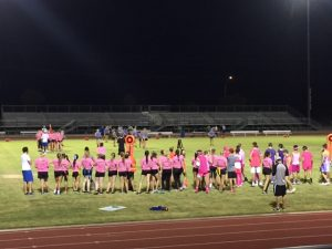 Senior powderpuff players cheer on their teammates while new players enter the game.