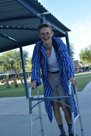 Stephan Cattermole, junior, carries a walker around campus to accompany the spirit day's reTIREDment theme.