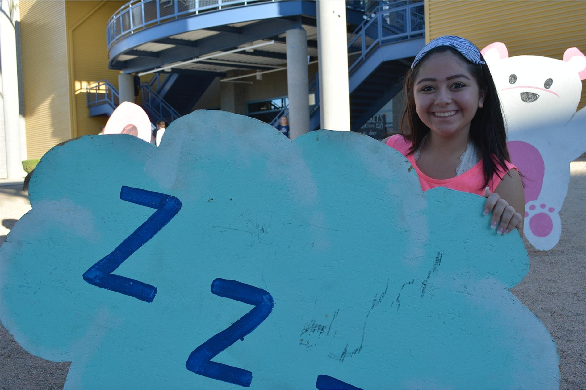 Mila Alarcon, sophomore, poses with a spirit week bulletin in her sleep attire to complement the spirit week theme.