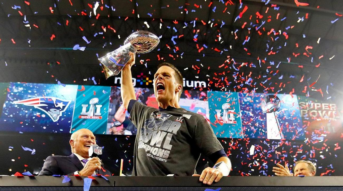 Tom Brady raises hand and holds up Vince Lombardi trophy after Super Bowl win