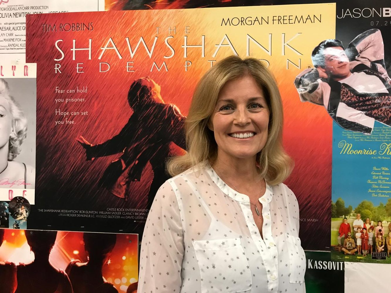 Photo by Lexi Gass. Susan Henry posed next to her the movie posters she always hangs in her room.