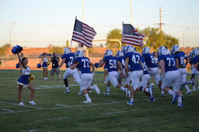 The+varsity+football+team+is+greeted+with+this+year%E2%80%99s+cheerleaders+as+they+run+down+the+field.