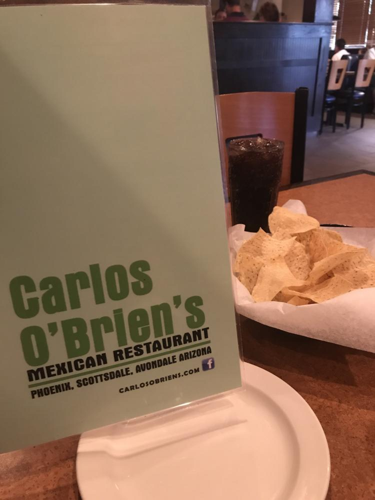 A menu, chips, and Dr. Pepper sit on a table at Carlos O'Brien's as customers decide what to order.