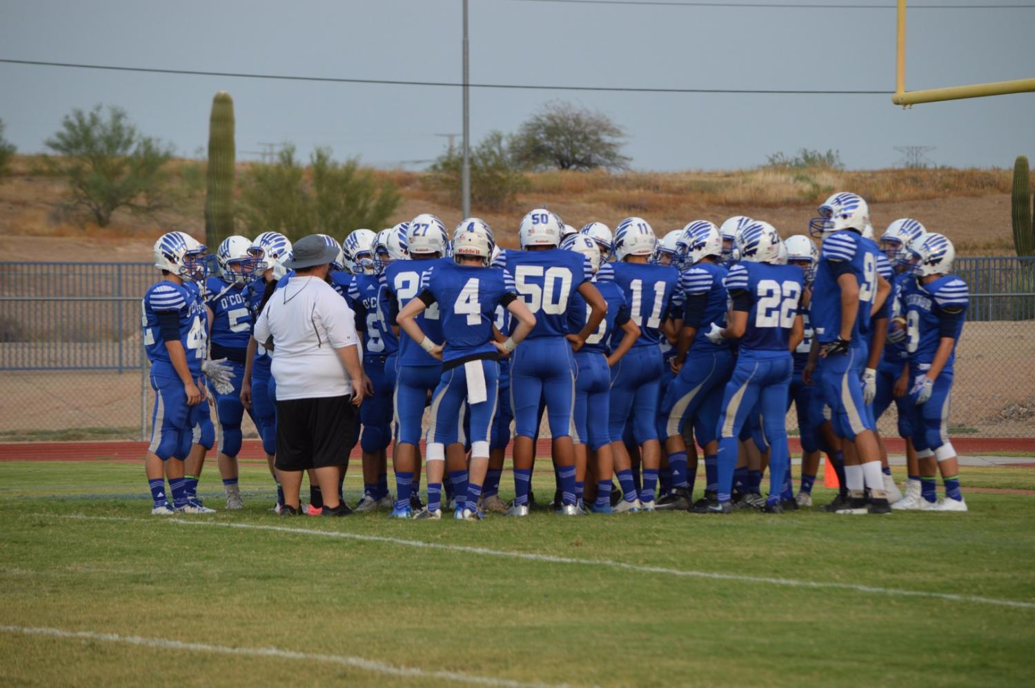 The JV football team huddle together to discuss their new game plan.