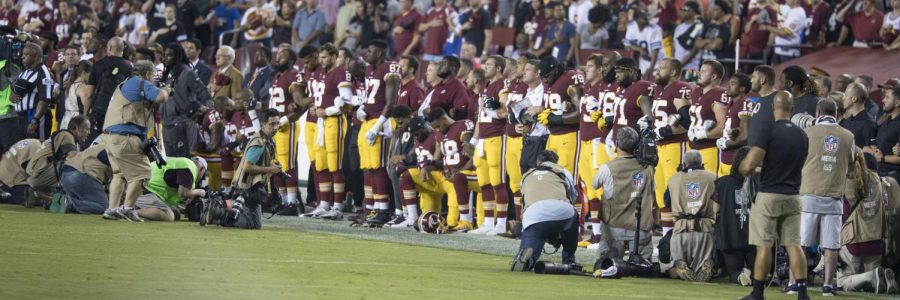 Players+of+the+Washington+Redskins+NFL+team+neal+in+pprotest+during+the+anthem