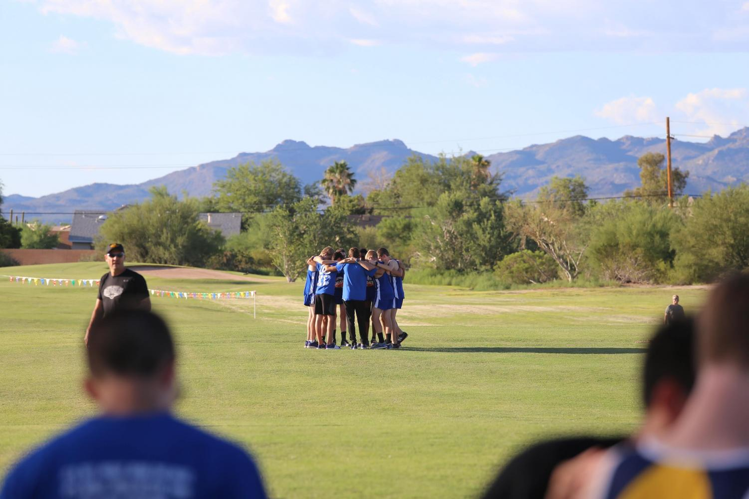 Cross country boys huddle together before the first race of the season