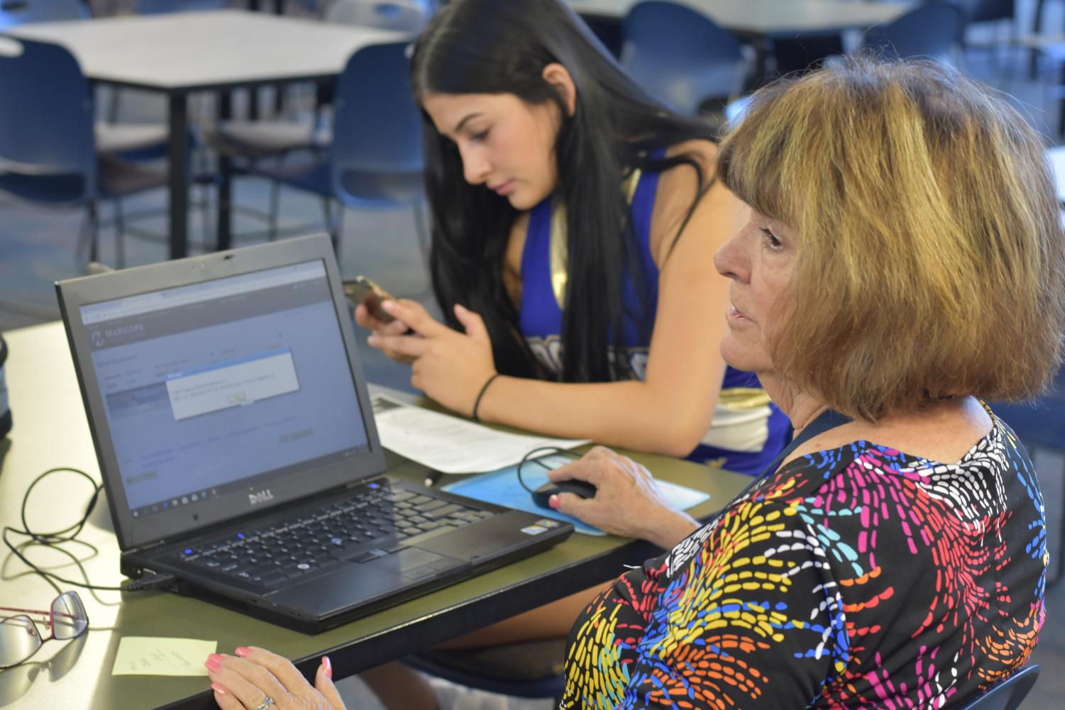 Ruby Miller, Rio Salado representative, helps a student register to a dual course in the OHS library.