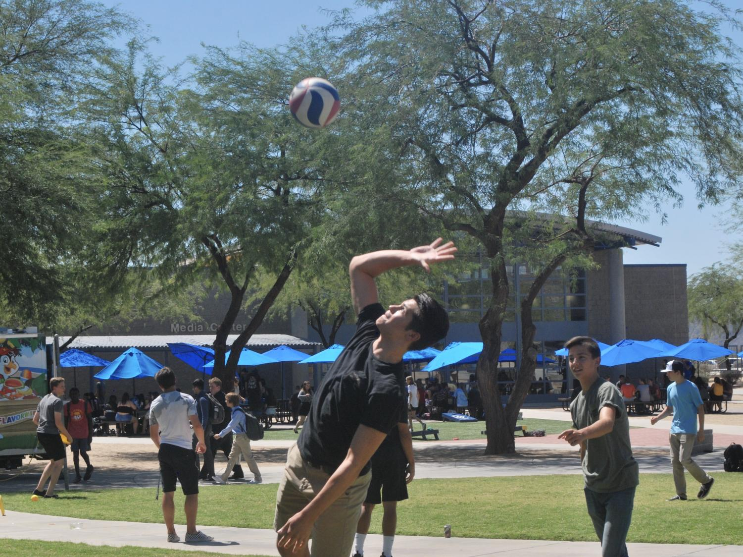 Sam Zaporowski passes Eagle Hour time by playing Volleyball near the center of campus