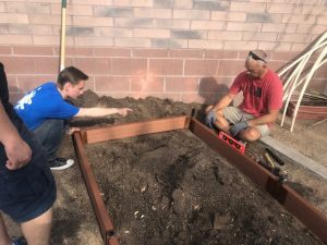 Ethan Badey (left) and Lt. Col Simmons (right) work in the ROTC garden, which is one of the many activities that ROTC participates in to support the community.