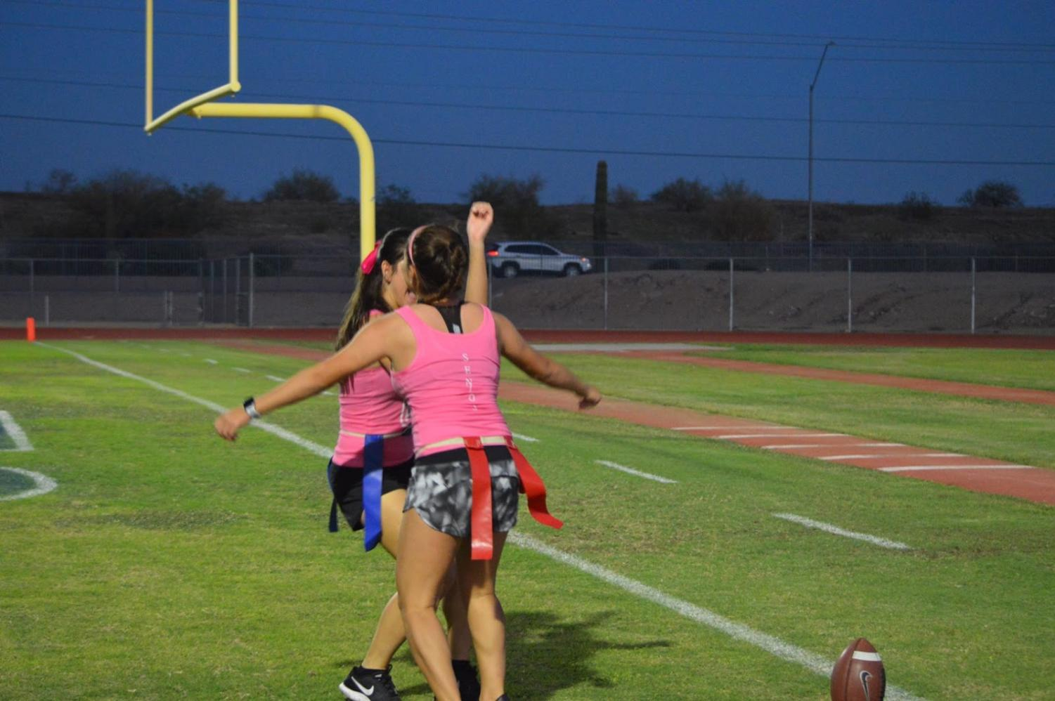Seniors chest bump to a victorious touchdown made against the juniors.