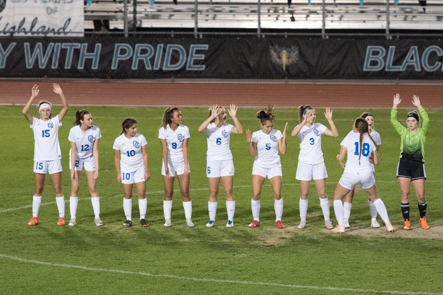 Varsity girls soccer prepares for their game by announcing their starting lineup for the night ahead.