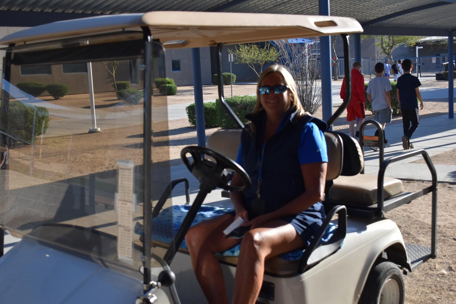 Darcy Wine, security staff, poses for a photo on one of the golf carts used to patrol the campus.