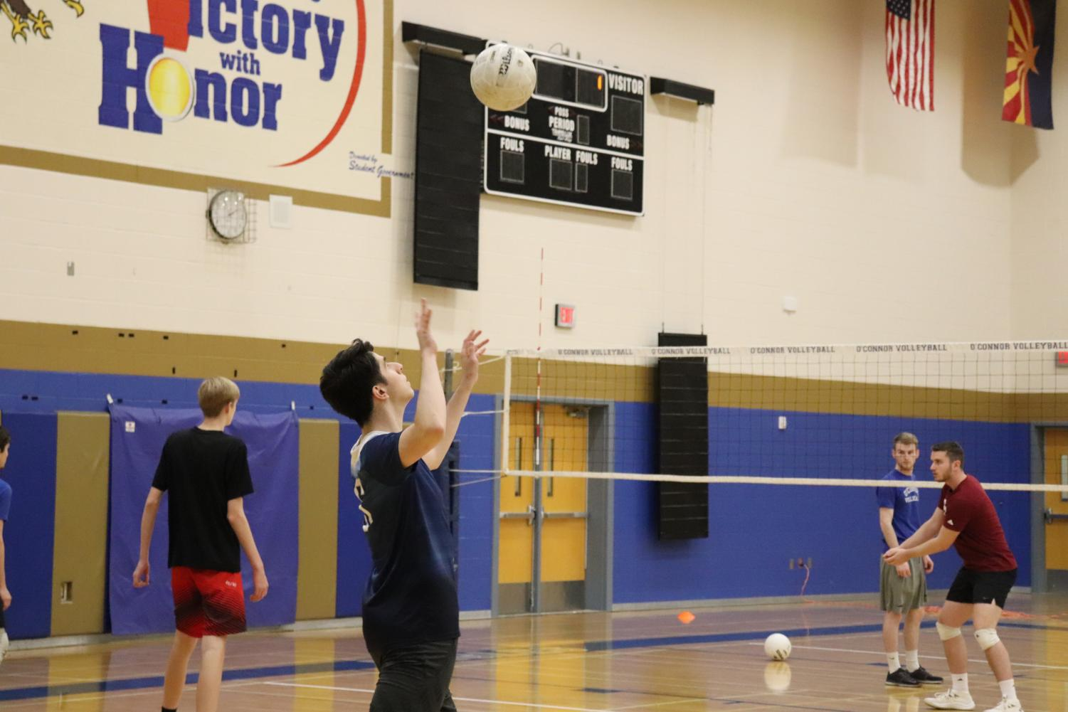 Diego Guillen. senior, looks to serve the ball at practice on February 27th.