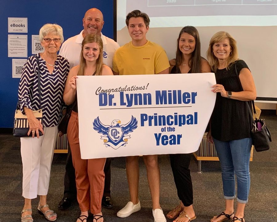 Dr. Lynn Miller standing beside his family as he receives Principal of the Year Award.