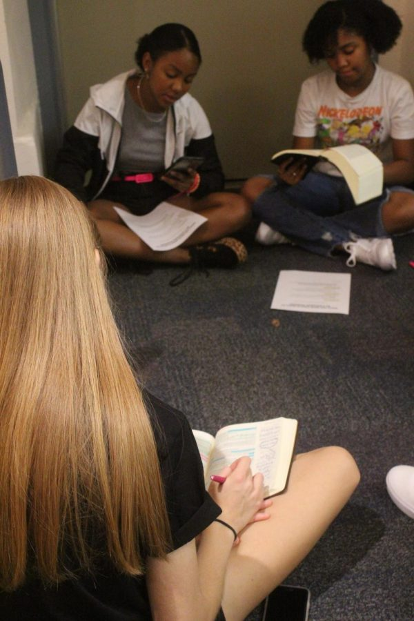 During+the+second+Kingdom+Workers+meeting%2C+sisters+JoJo+Roberts%2C+senior%2C+and+Julia+Roberts%2C+freshman+sit+in+a+circle+to+read+and+discuss+the+passage.