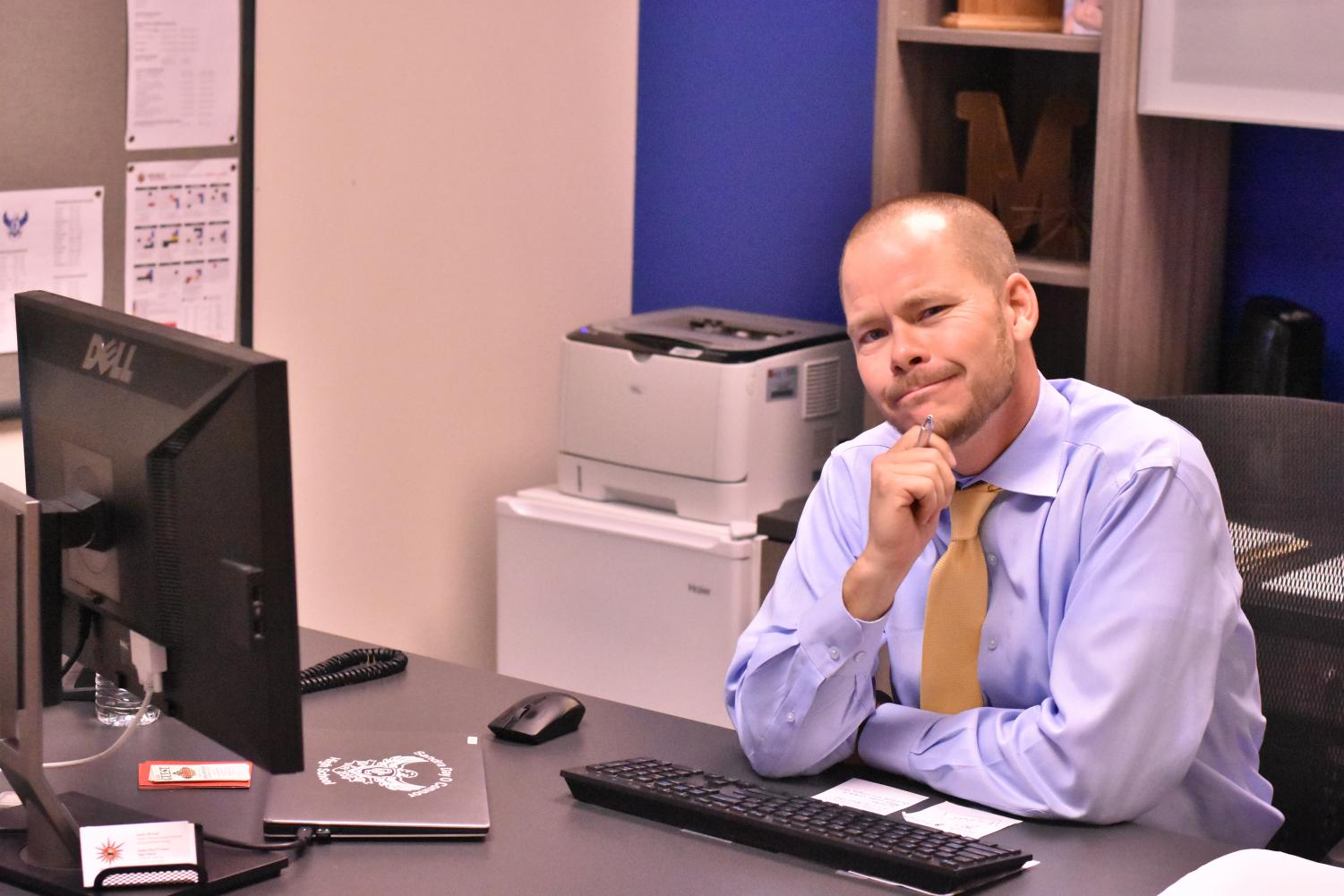 Mr. McLain makes a goofy countenance while working in his office.