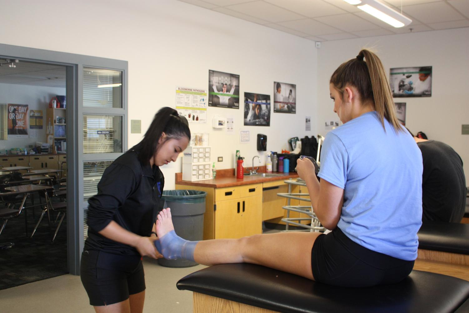 Student intern wraps up athlete's ankle in between practices.