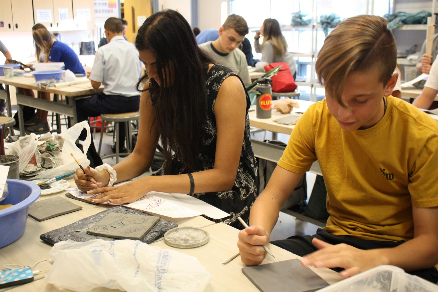 Tanner Valus, sophomore, and Akshara Taikella, senior, carefully etch out their designs on the clay tiles.