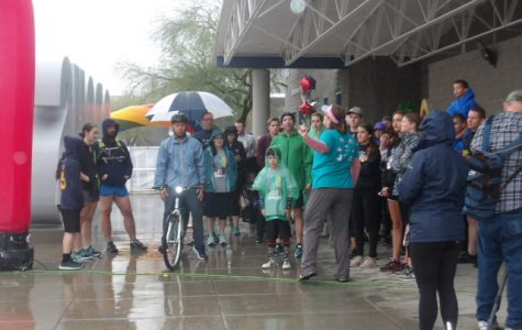 Racers stand at the start line, gearing up to begin their race in the rain.