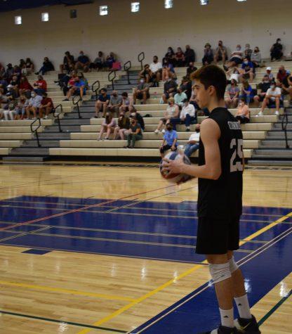 Sevastian Malcom, junior, preparing to serve against his opponent, LHS.